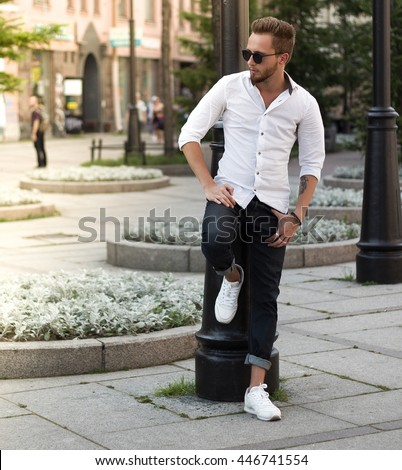 Portrait of young stylish man  in the street, life style.