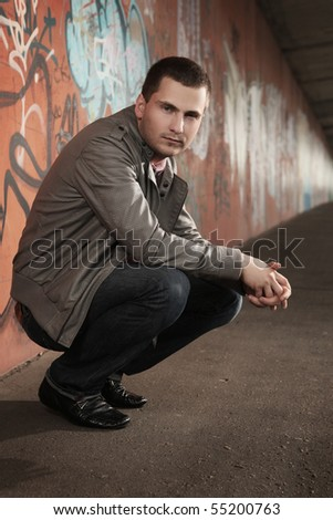 portrait of young stylish man sitting in tunnel - stock photo
