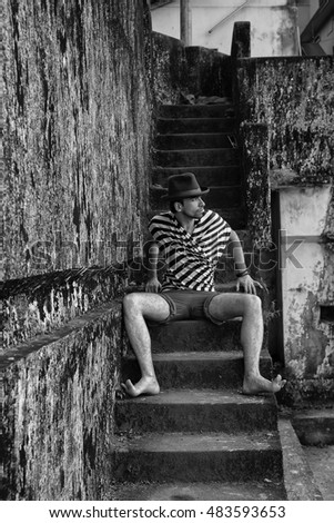 Portrait of young stylish man sitting on the steps. Fashion style