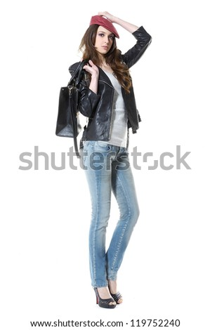 Portrait of young stylish woman in jeans with handbag posing in studio - stock photo