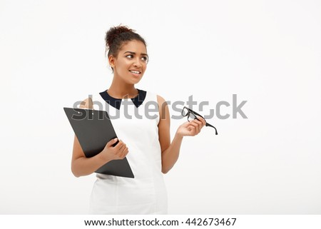 Portrait of young successful african business lady holding folder and glasses, smiling over white background. Copy space.