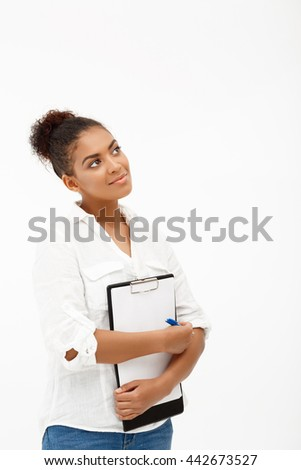 Portrait of young successful african business lady holding folder, smiling over white background. Copy space.