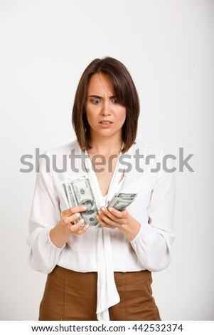 Portrait of young successful business woman counting money over white background.