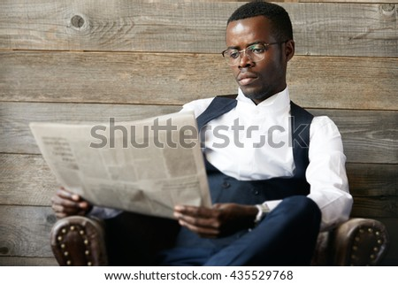 Portrait of young successful confident dark-skinned CEO in elegant suit, busy reading financial news with captured concentrated expression, relaxing in leather armchair. Business and career concept - stock photo