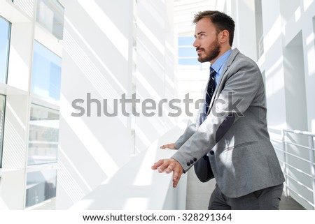 Portrait of young successful man financier thinking about something while looking in big office window, confident serious businessman dressed in formal wear enjoying calm and rest after hard work day  - stock photo