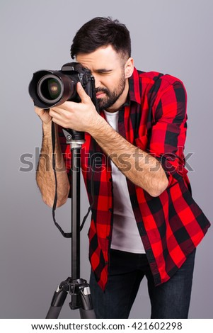 Portrait of young successful photographer taking photos in studio - stock photo