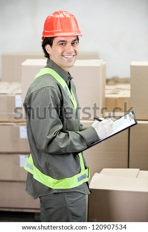 Portrait of young supervisor writing notes at warehouse - stock photo