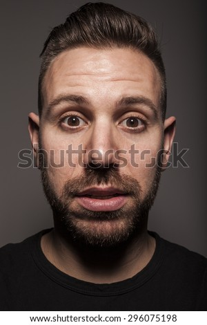 Portrait of young surprised man in studio setting and casual outfit - stock photo