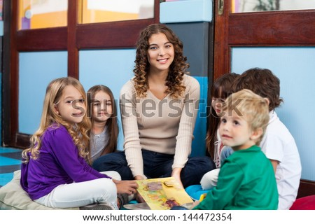Portrait of young teacher and children with book sitting on floor in classroom - stock photo