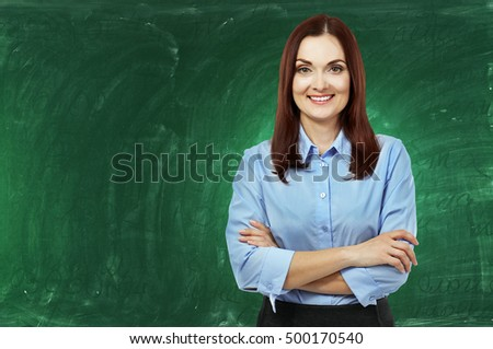 Portrait of young teacher on chalkboard background