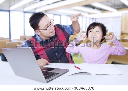 Portrait of young teacher talking with female student while the student closing her ears in the classroom - stock photo