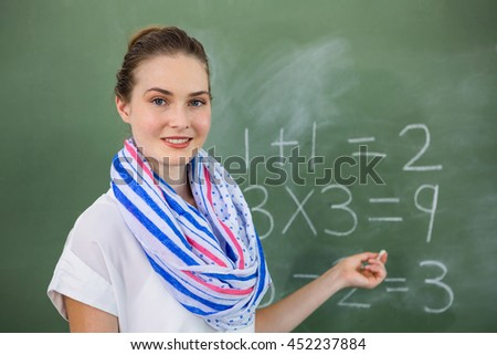 Portrait of young teacher teaching mathematics on chalkboard in classroom