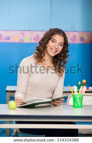 Portrait of young teacher with book sitting at desk in classroom - stock photo