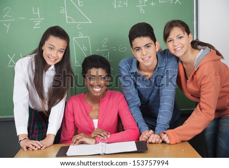 Portrait of young teacher with high school students at desk in classroom - stock photo