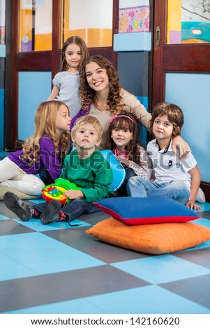 Portrait of young teacher with students sitting together on floor in classroom - stock photo