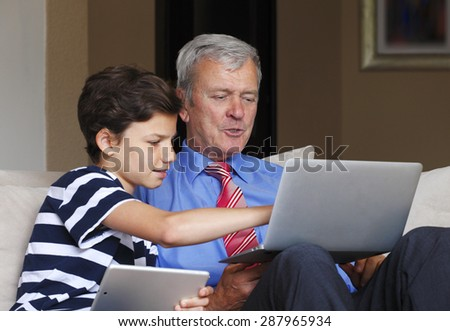 Portrait of young teenager boy with digital tablet sitting at sofa at home with his grandfather and teaching how to use the laptop. Grandson points out the screen of the laptop.  - stock photo