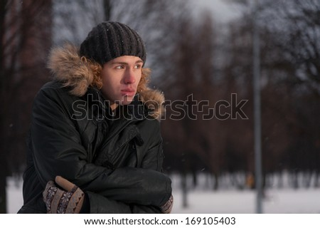 Portrait of young thoughtful man in the Park at winter