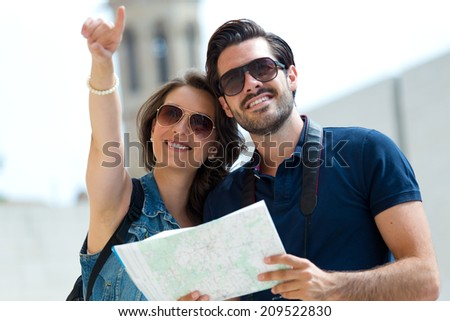 Portrait of young tourist couple use their map and pointing where they want to go. - stock photo
