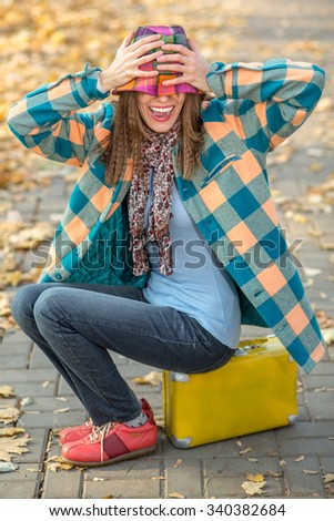 Portrait of young traveler in autumn landscape having fun while sitting on  yellow suitcase - stock photo