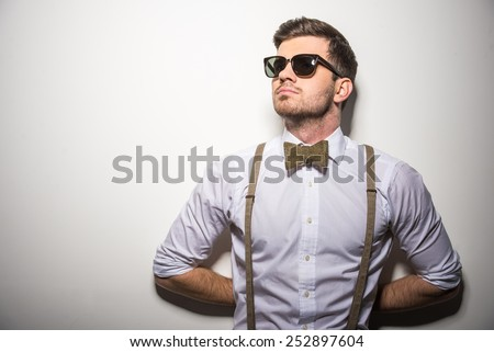 Portrait of young trendy man with black glasses, suspenders and bow-tie on gray background. - stock photo