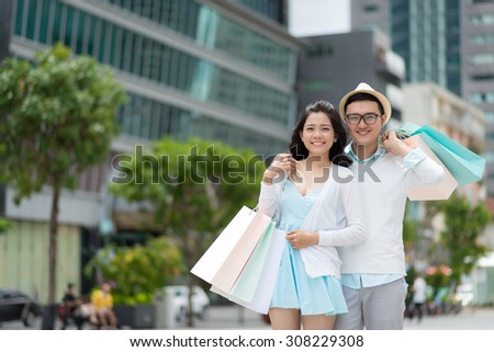 Portrait of young Vietnamese couple after having shopping in the city - stock photo