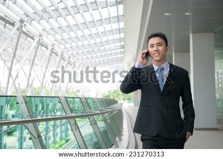 Portrait of young Vietnamese manager talking on the phone