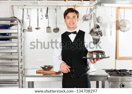 Portrait of young waiter with cloche lid cover and tray standing in commercial kitchen