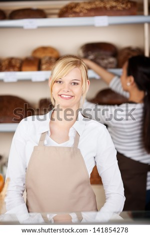 Portrait of young waitress smiling with coworker working in background at cafe - stock photo