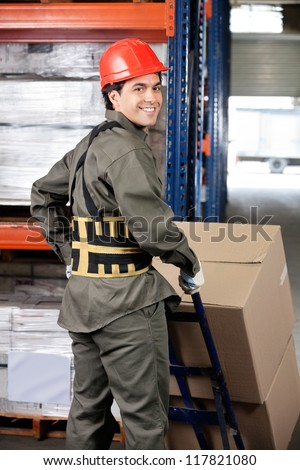 Portrait of young warehouse worker pushing handtruck with cardboard boxes - stock photo