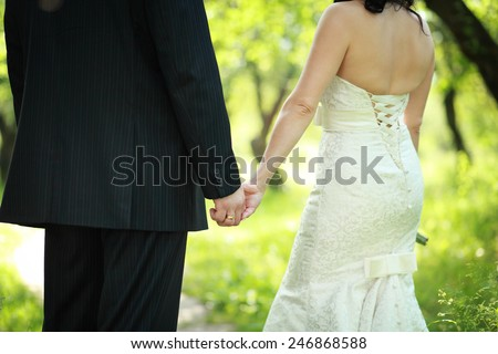 Portrait of young wedding couple, back view, outdoor - stock photo