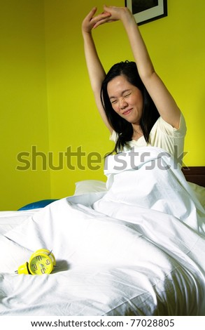 portrait of young woman and alarm clock in bedroom - stock photo