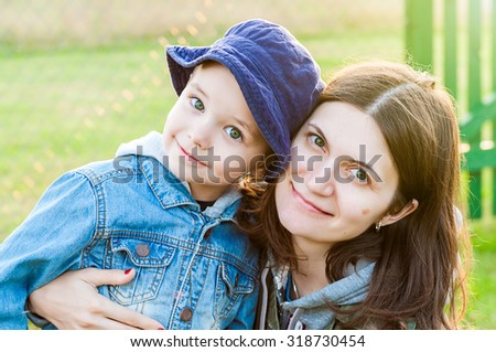 portrait of young woman and boy mother and son family in summer sunshine over green - stock photo