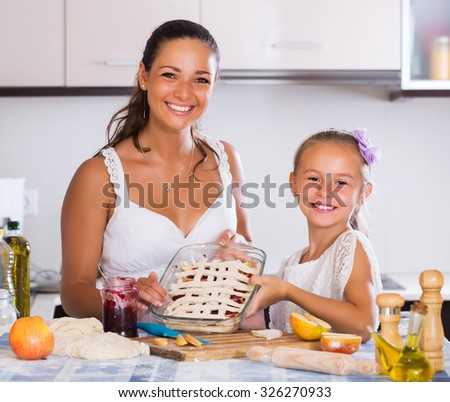 Portrait of young woman and child cooking apple strudel
