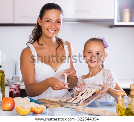 Portrait of young woman and child cooking apple strudel in kitchen