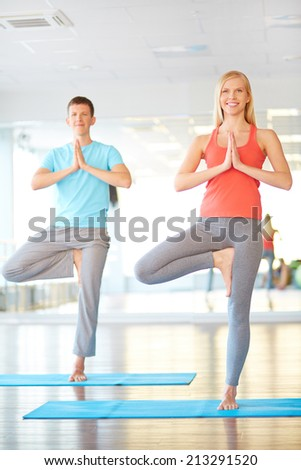 Portrait of young woman and man doing yoga exercise in gym - stock photo