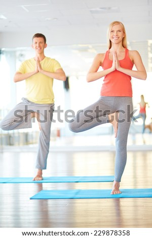Portrait of young woman and man doing yoga exercise on mats - stock photo