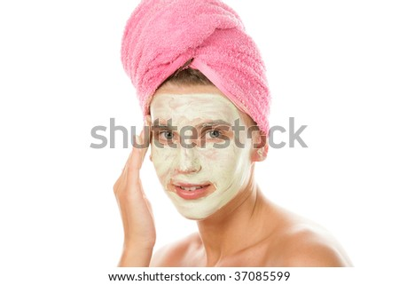 Portrait of young woman applying facial cream and drying hair with towel isolated on white background - stock photo