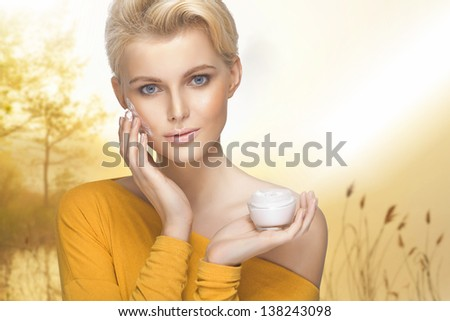 Portrait of young woman applying moisturizer cream on her pretty face - stock photo
