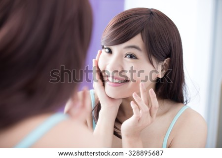 Portrait of young woman applying moisturizer cream on her pretty face and look mirror. asian beauty