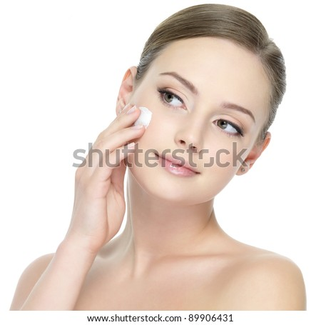 Portrait of young woman applying moisturizer cream on her pretty face - white background