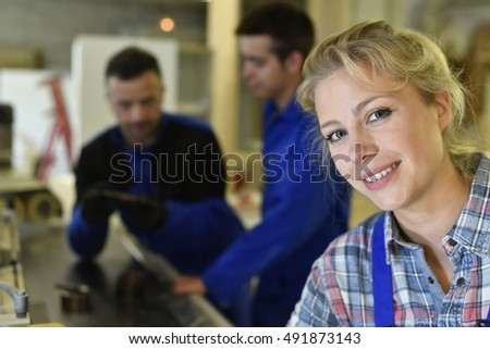 Portrait of young woman apprentice in workshop