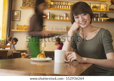 Portrait of young woman at a coffee shop, Beijing - stock photo
