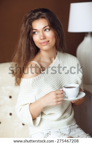 Portrait of Young Woman at Home Sipping Tea from a Cup - stock photo