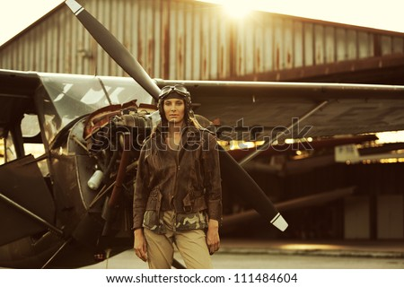 Portrait of young woman aviator, airplane and hangar on background - stock photo