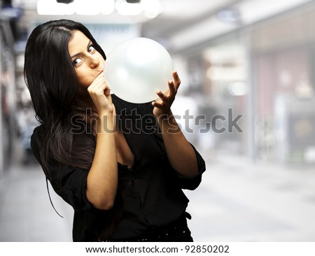 portrait of young woman blowing balloon at a crowded place