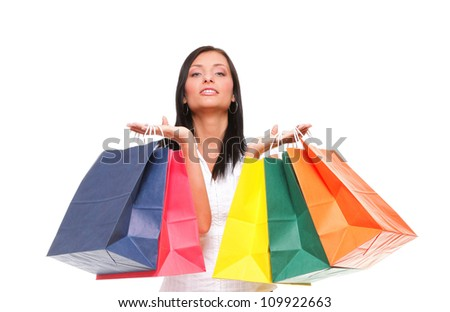 Portrait of young woman carrying shopping bags against white background