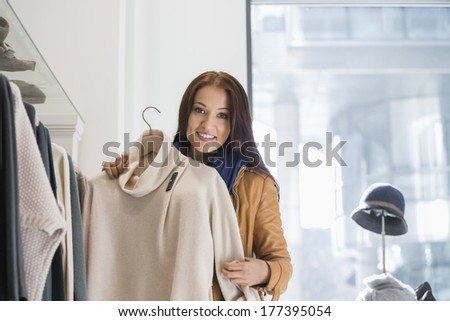 Portrait of young woman choosing sweater in store - stock photo