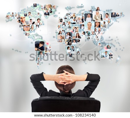 Portrait of young woman communicating with her friends across the world. Sitting against world map with photo of people. International communications concept - stock photo
