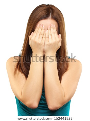 Portrait of young woman covering her face with hands. Studio shot, white background. - stock photo