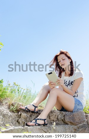 portrait of young woman cute brunette girl holding white tablet pc computer reading ebook sitting alone on stone & looking at screen on green summer outdoor blue sky copy space background picture - stock photo